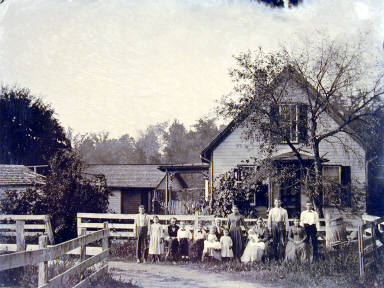 Family in front of Clapboard Fence and Farmhouse