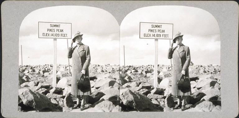 Woman at sign at summit of Pikes Peak