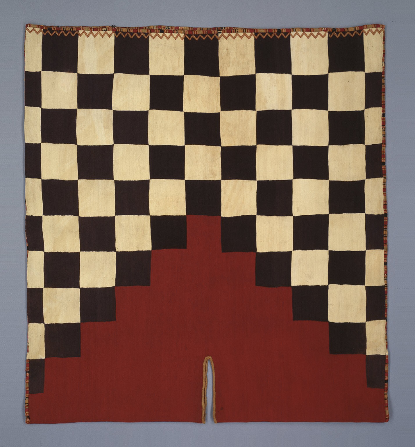 Tunic with checkerboard pattern and stepped yoke
