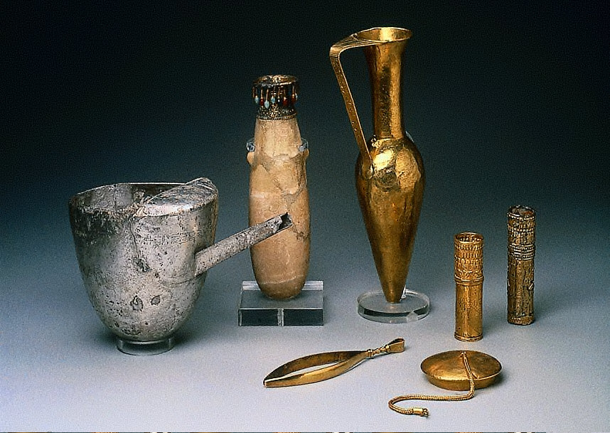 a) Spouted milk vessel inscribed for Aspelta's father, Senkamanisken; b) Albastron; c) Ewer; d-e) Cylinder sheaths; f) Tweezers of King Aspelta; g) Vessel lid with braided chain