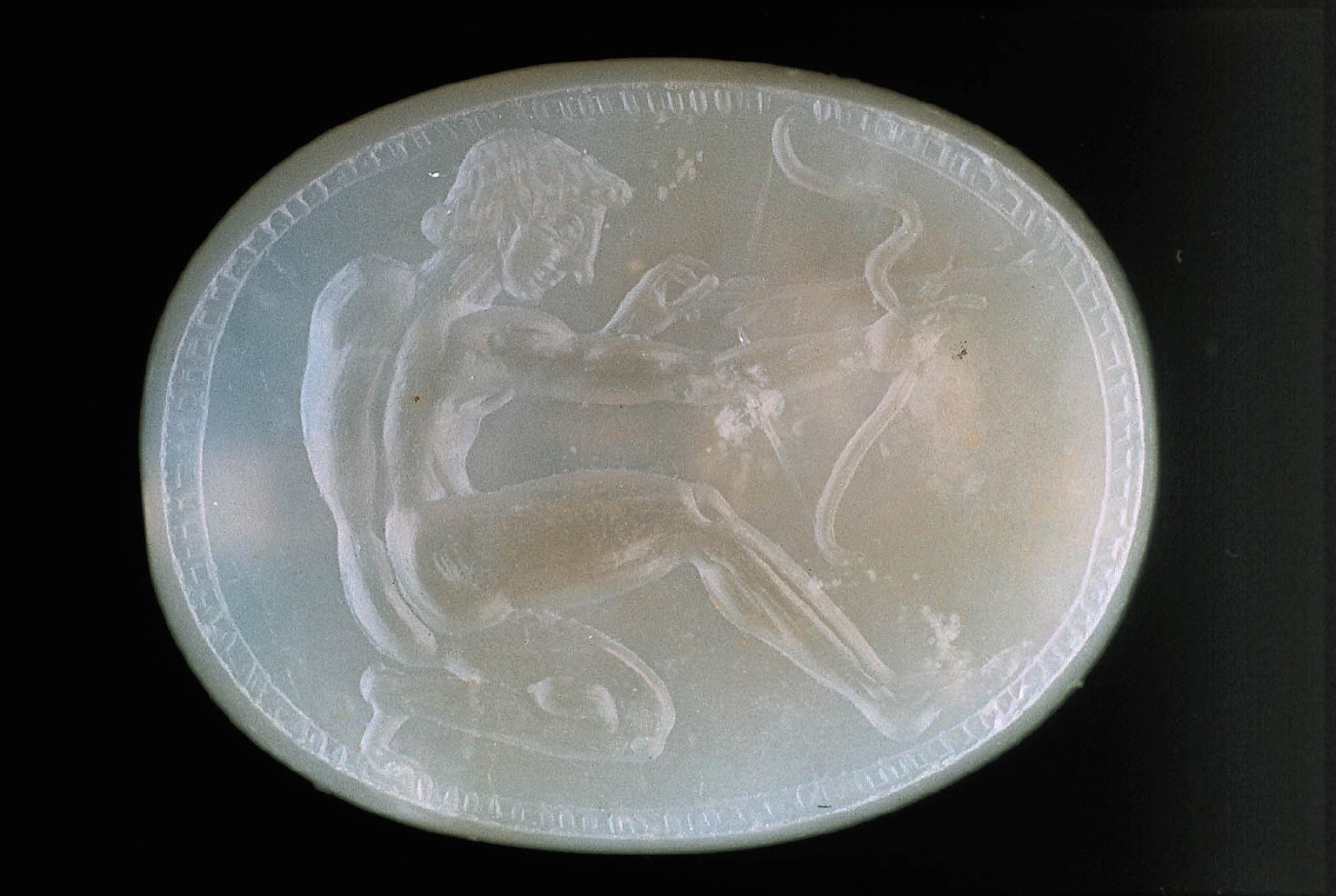 Scaraboid intaglio with kneeling youth drawing a bow