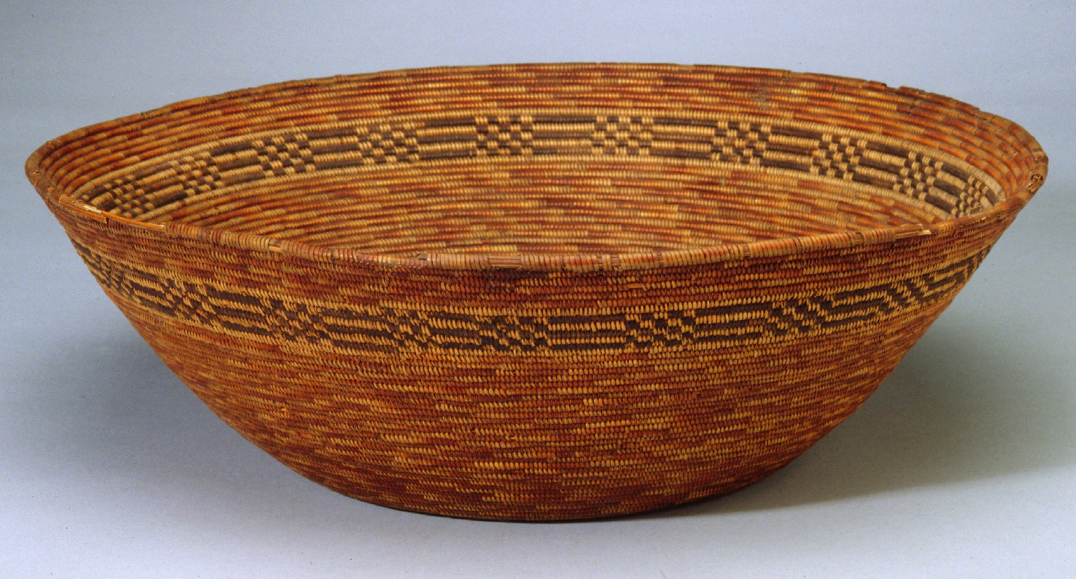 Coiled basket dark brown with black and red designs