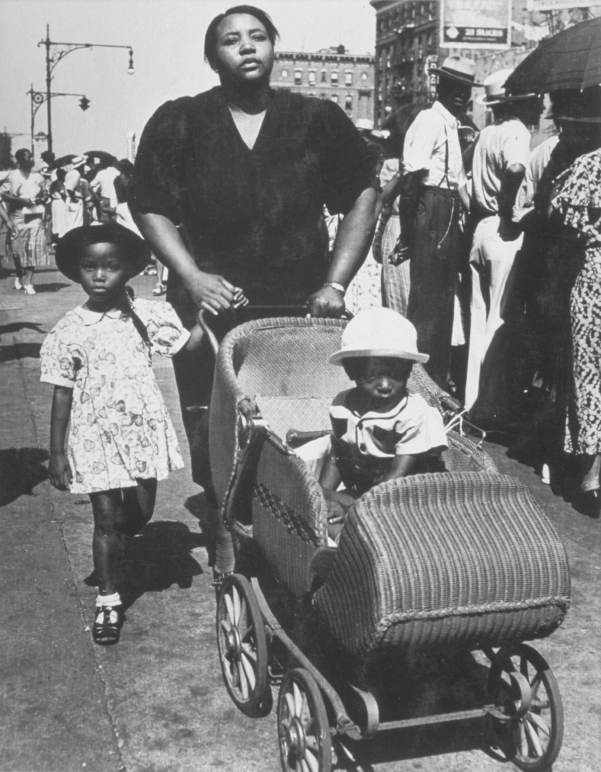 Family walking down street with buggy