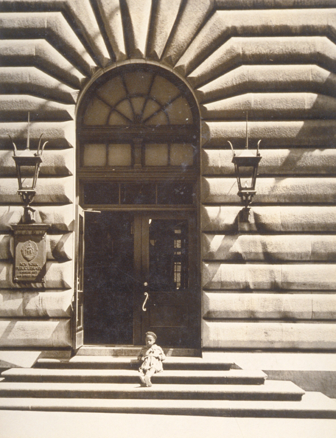Child sitting on step of New York Public Library
