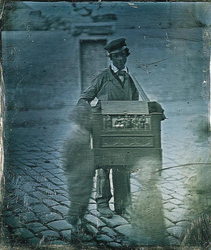 Organ Grinder on street with children passing