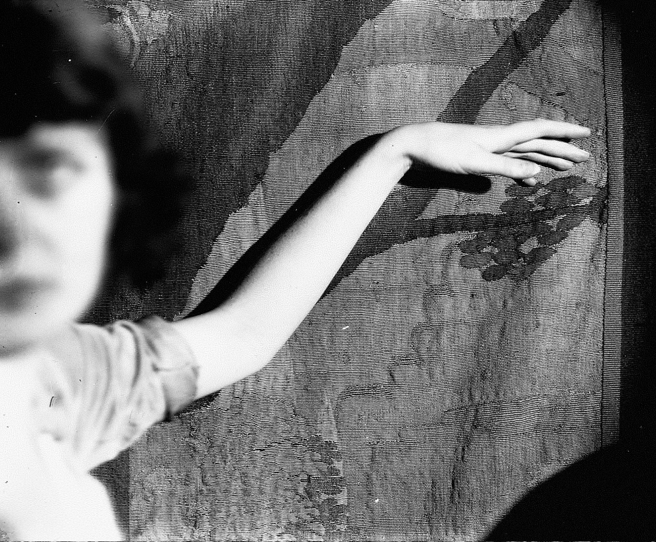 Woman with arm against wall