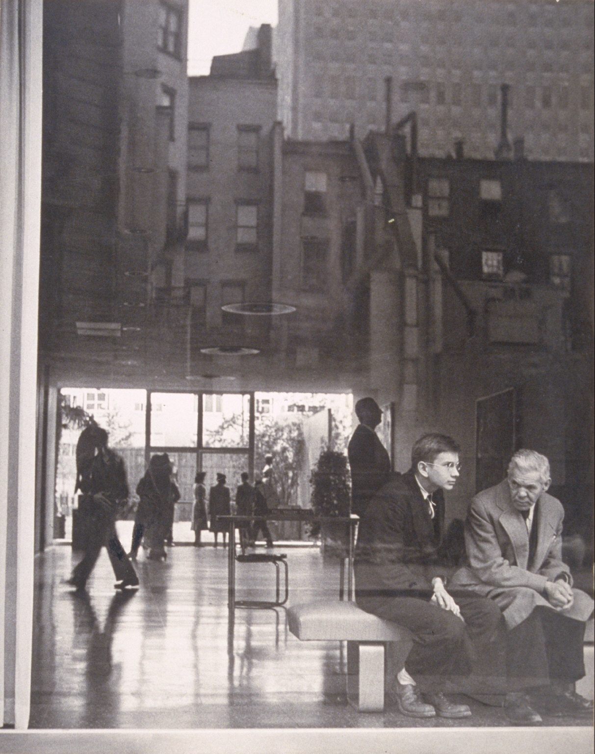 Two men sitting in lobby, Museum of Modern Art, NY