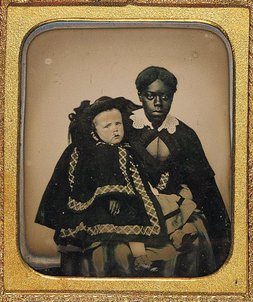Portrait of black woman holding white child