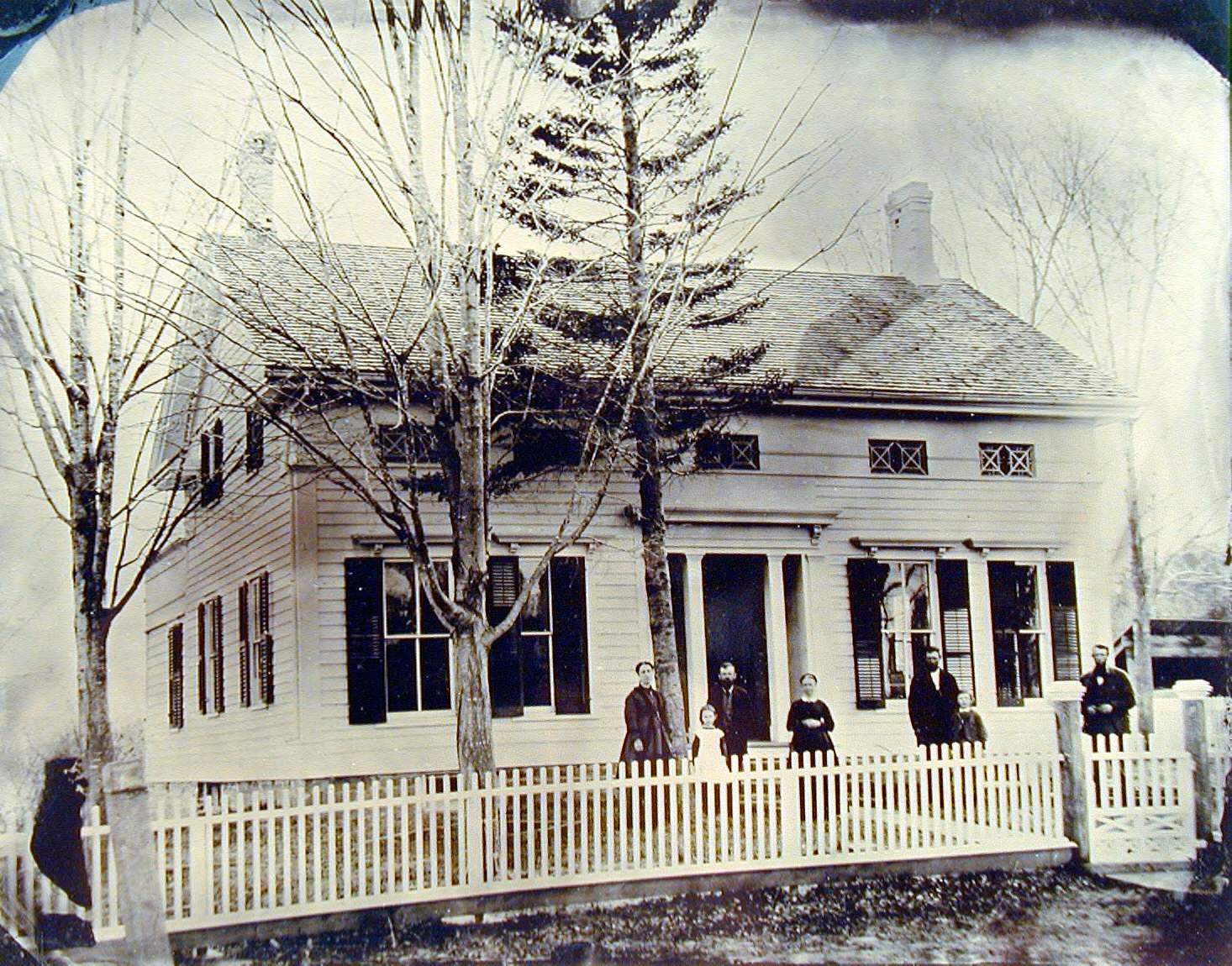 Family in front of Farm House and Picket Fence